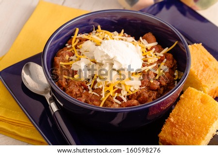 Serving of elk meat chili with red beans, sour cream, shredded cheese and diced onions in blue bowl and cornbread side - stock photo