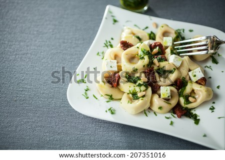Serving of feta cheese, basil and pine nut pesto with Italian tortellini pasta on a modern curved white plate over a grey cloth with copyspace - stock photo
