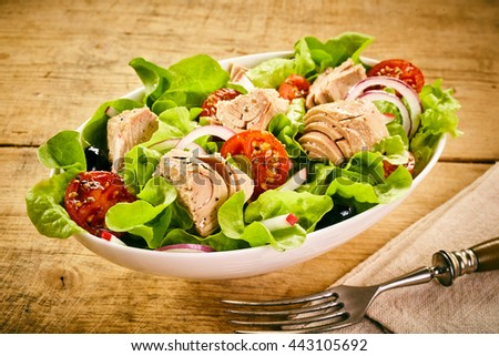 Serving of fresh tuna salad with lettuce, tomato, olives and onion in a white bowl on a rustic wooden table with fork and napkin, high angle view - stock photo