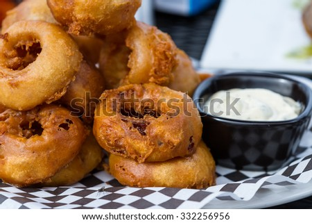 serving of fried onion rings served with a dipping sauce - stock photo