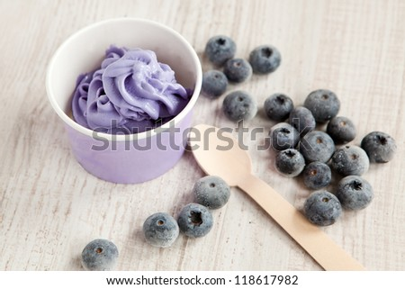 Serving of frozen creamy ice yogurt  with whole fresh blueberries and wooden spoon - stock photo