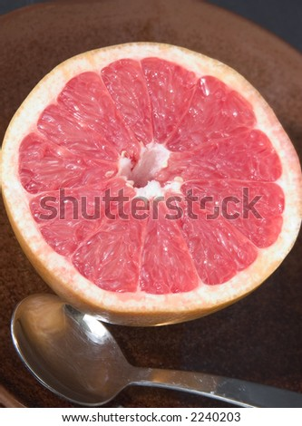 Serving of half pink grapefruit on a plate with spoon - stock photo