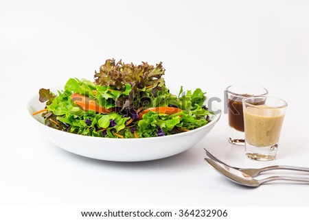 Serving of healthy vegetables salad and dressing on white background. - stock photo