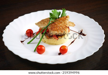 Serving of mashed potato with tasty baked fish - stock photo
