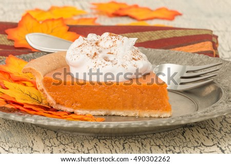 Serving of pumpkin pie with whipped cream photographed closeup.