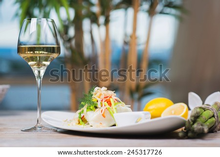 serving of steamed sea bass fillet on a plate in a restaurant, on a wooden table with white wine and decor - stock photo