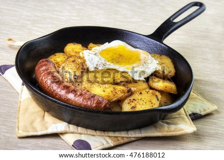 Serving pan fried potatoes , sausage and egg on cast iron skillet