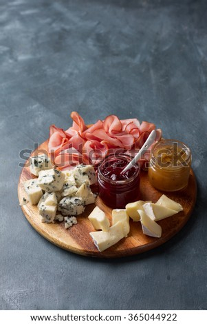 Serving platter with bacon,  cheese and sauce on a dark background - stock photo