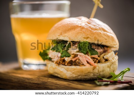 serving pub food, pork bap with coleslaw, on wooden board with cider