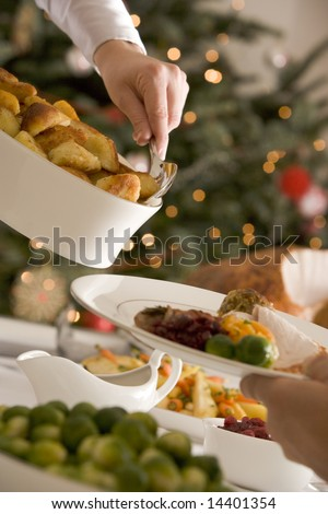 Serving Roast Potatoes at Christmas Lunch - stock photo
