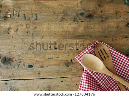 Serving spoons on checkered cloth lying on wooden surface - stock photo