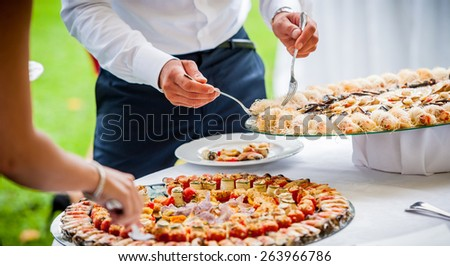 Serving tasteful food, catering, wedding, cook and chef - stock photo
