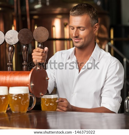 Serving the best beer in town. Handsome bartender in white shirt serving beer - stock photo