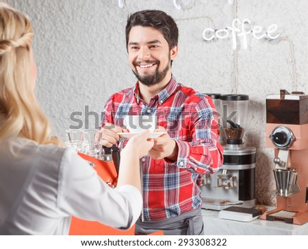 Serving with pleasure. Smiling man with beard getting cup of coffee from female barista. - stock photo