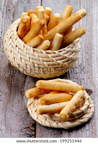Sesame Bread Sticks in Wicker Bowls isolated on Rustic Wooden background - stock photo