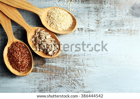 Sesame, flax and sunflower seeds in wooden spoons on blue background, closeup - stock photo