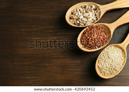 Sesame, flax and sunflower seeds in wooden spoons on table, closeup - stock photo
