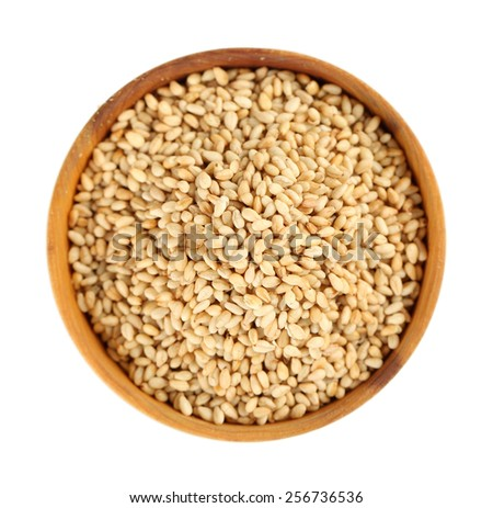 Sesame in wooden bowl, isolated on white - stock photo
