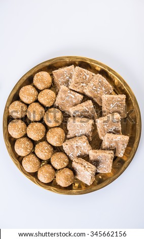 sesame laddu or tulgul or til gul laddu or ladu, sesame and jaggery sweet cake with spread coconut, favourite sweet dish in Makar Sankranti Festival in India, 14 january, indian festival sweets