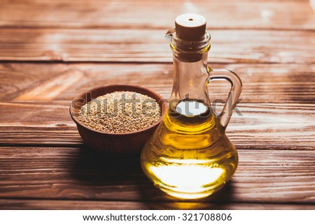 Sesame oil in a glass bottle with a cork and heap sesame seeds in a wooden bowl - stock photo