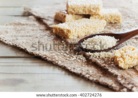 Sesame seed and sesame dessert with caramel on a linen tablecloth. Kozinak sesame seeds. Shallow DOF. With copy space - stock photo