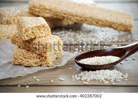 Sesame seed and sesame dessert with caramel on wooden background. Kozinak sesame seeds. Shallow DOF - stock photo