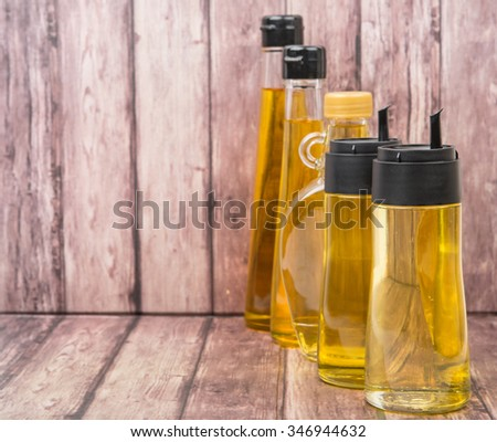 Sesame seed oil, flax seed oil, olive oil, corn oil and vegetable oil in bottles over wooden background