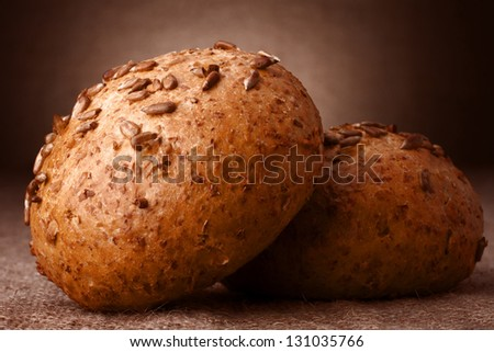 Sesame seeds buns on rustic background - stock photo