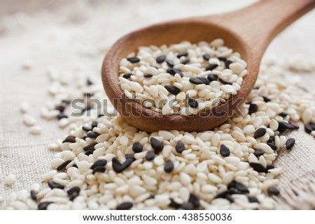 Sesame seeds in a wooden spoon closeup - stock photo