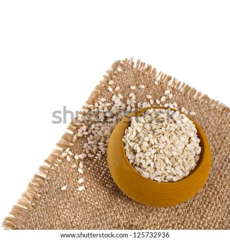Sesame seeds isolated in sackcloth on white background - stock photo