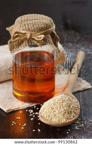 Sesame seeds on a wooden spoon and sesame oil in a glass jar. - stock photo
