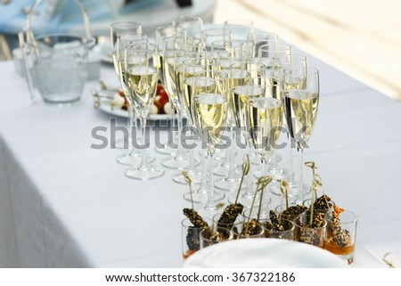 Set a variety of sweets, glasses with white champagne on table outdoors to celebrate the solemn event. Catering business. - stock photo