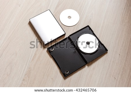 Set dvd or cd disc cover case mockup with open plastic box. Template disc with white isolated free space for design. Mock up with black package for compact or dvd disc. On wooden table background - stock photo