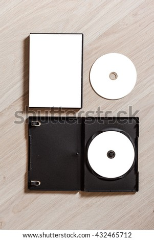 Set dvd or cd disc cover case mockup with open plastic box. Template disc with white isolated free space for design. Mock up with black package for compact or dvd disc. On wooden table background. Top - stock photo