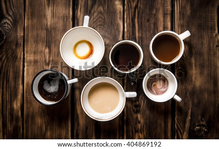Set empty and full cups of coffee. On black rustic background. - stock photo