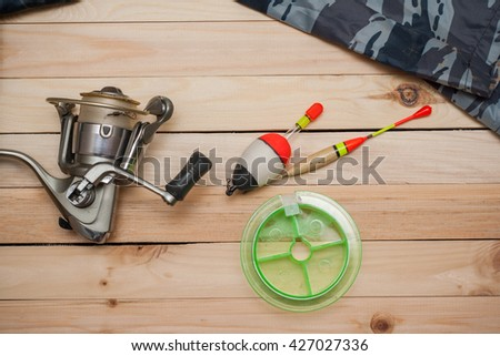 Set for fishing on the wooden background with camouflage clothing. Coil, colored floats, fishing line. Fishing and recreation. - stock photo
