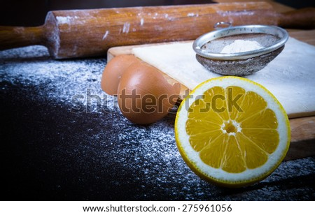 Set for home baking on a black background with flour. Rolling pin, dough, half of lemon, baking form, eggshell. Toned. - stock photo