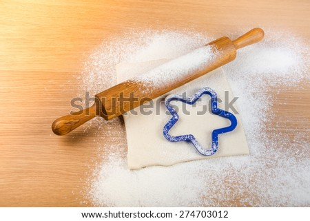 Set for home baking on a light wooden table with flour. Rolling pin, baking form, dough. Toned. - stock photo