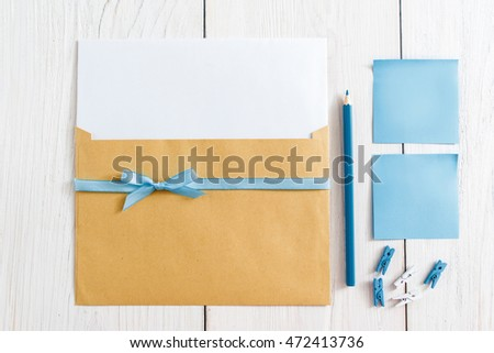 Set for making handmade greeting card, flat lay. Top view on kit of envelope with blank paper and blue ribbon, pencil, pins and sticker on white background. It's a boy note concept