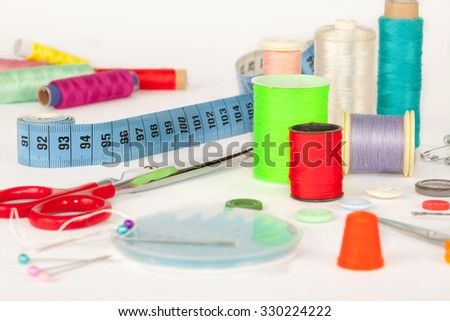 Set for needlework,Sewing kit. Scissors, bobbins with thread, measure tape, Iron and needles - stock photo