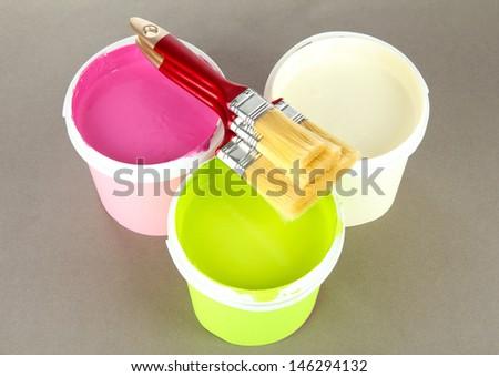 Set for painting: paint pot, brushes on grey background - stock photo