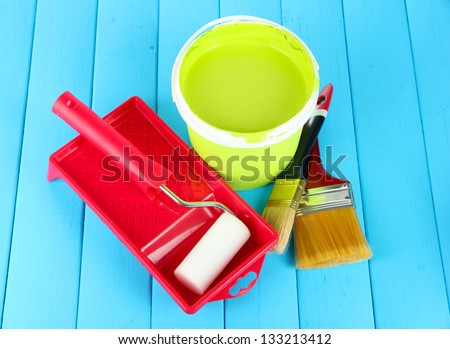 Set for painting: paint pot, brushes, paint-roller on blue wooden table - stock photo