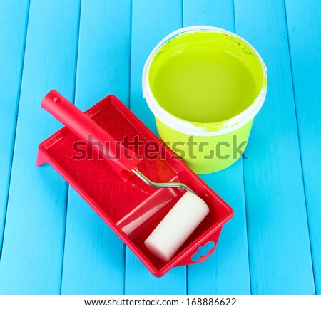 Set for painting: paint pot, paint-roller on blue wooden table - stock photo