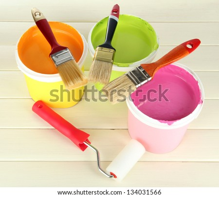Set for painting: paint pots, brushes, paint-roller on white wooden table - stock photo