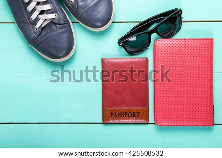 set for traveling, passport, e-book, sneakers, sunglasses. on a wooden turquoise  surface, a top view