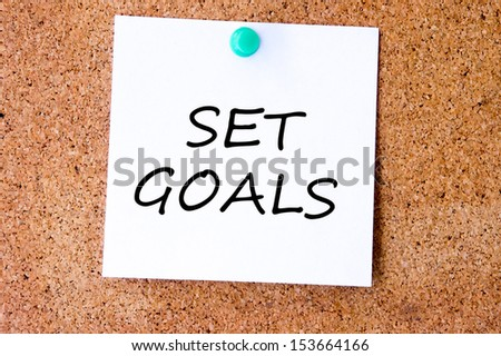 Set Goals on white sticky note pinned with blue push pin on cork board