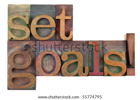 Set goals reminder in vintage wooden letterpress type blocks, stained by color ink, isolated on white