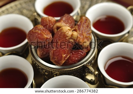 Set of Arabic tea cups with date fruits. Close up. - stock photo