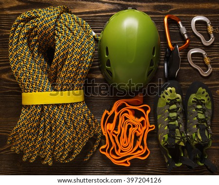 set of basic climbing equipment on rough wood - stock photo