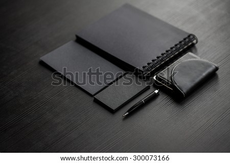 Set of black mockups on dark background,  female hand holding a business card - stock photo